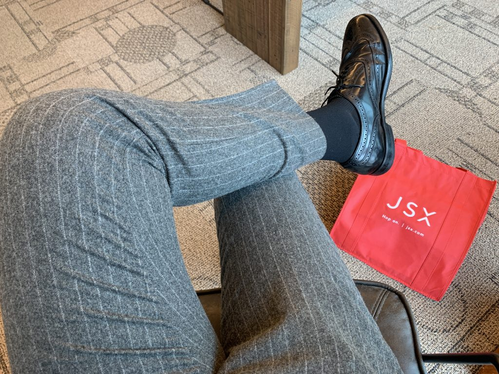 Waiting in the JSX Houston lounge with a JSX-branded tote bag.