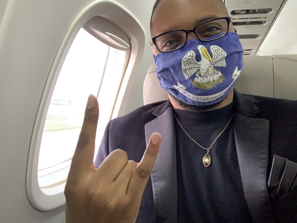 Onboard JSX in a Louisiana state flag face mask. By federal law, masks are required on all JSX flights and in all airport facilities.